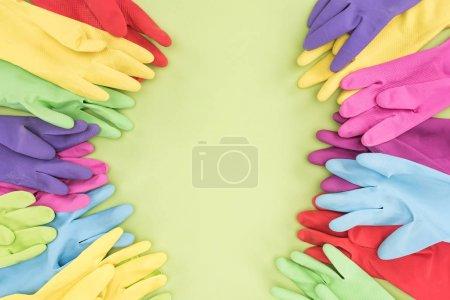Photo pour Vue de dessus des gants en caoutchouc multicolores sur fond vert avec espace de copie - image libre de droit