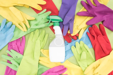 Photo for Top view of messy scattered multicolored rubber gloves and white spray bottle with cleanser on green background - Royalty Free Image