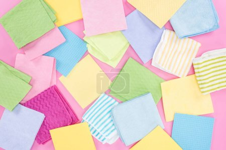 Foto de Vista superior de los trapos multicolores dispersos desordenados sobre fondo rosa - Imagen libre de derechos