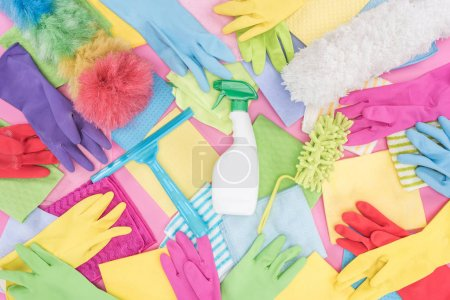 Photo for Top view of messy scattered multicolored cleaning supplies on pink background - Royalty Free Image