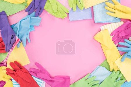 Foto de Vista superior de trapos multicolores dispersos desordenados y guantes de goma en el fondo rosa con espacio de copia - Imagen libre de derechos