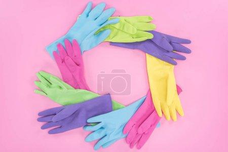 Photo pour Cadre en gants de caoutchouc multicolores sur fond rose avec espace de copie - image libre de droit