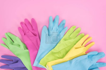 Photo for Top view of multicolored rubber gloves on pink background - Royalty Free Image