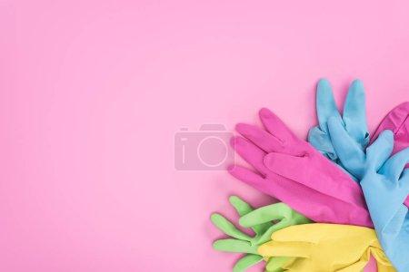 Foto de Top view of multicolored rubber gloves on pink background with copy space - Imagen libre de derechos