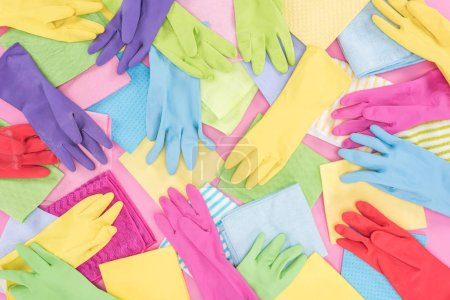 Foto de Top view of messy scattered multicolored rags and rubber gloves on pink background - Imagen libre de derechos
