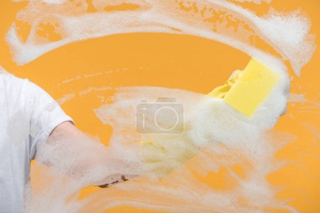 Photo for Cropped view of cleaner in rubber glove cleaning glass with sponge on orange background - Royalty Free Image