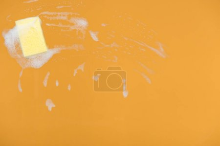 Photo pour Yellow sponge with foam on orange background - image libre de droit