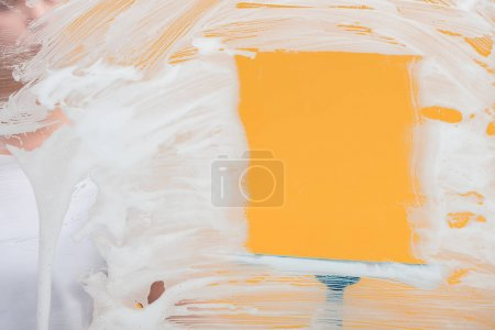 Photo for Selective focus of cleaner using squeegee while cleaning window from foam - Royalty Free Image