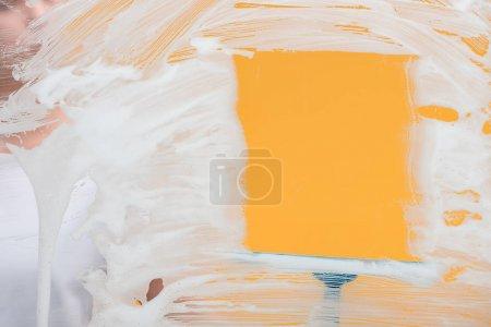 Photo pour Mise au point sélective de nettoyant à l'aide de squeegee tout en nettoyant la fenêtre de la mousse - image libre de droit