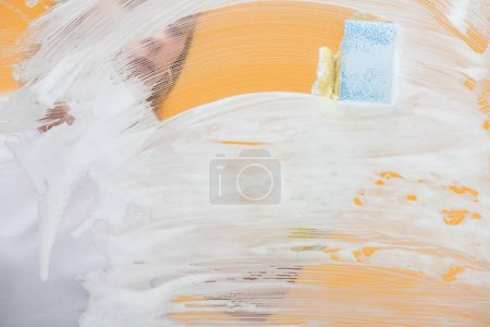 Photo for Young woman in rubber glove with sponge cleaning glass covered with foam - Royalty Free Image
