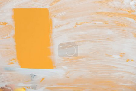 Photo for Squeegee near glass covered with white foam on orange background - Royalty Free Image
