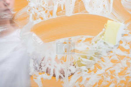 Photo pour Vue recadrée de jeune femme dans le gant en caoutchouc avec le verre de nettoyage d'éponge couvert de mousse - image libre de droit