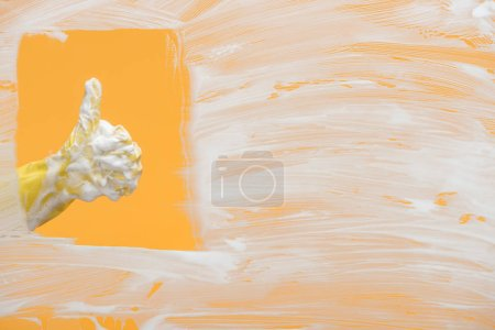 Photo for Cropped view of cleaner in yellow rubber glove with foam showing thumb up - Royalty Free Image