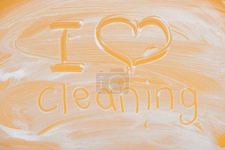Photo pour J'aime nettoyer le lettrage manuscrit écrit sur le verre avec la mousse blanche sur le fond orange - image libre de droit