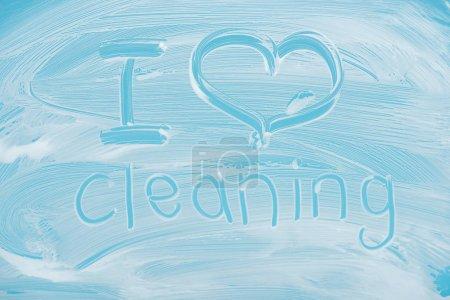 Photo pour J'aime nettoyer le lettrage manuscrit écrit sur le verre avec la mousse blanche sur le fond bleu - image libre de droit