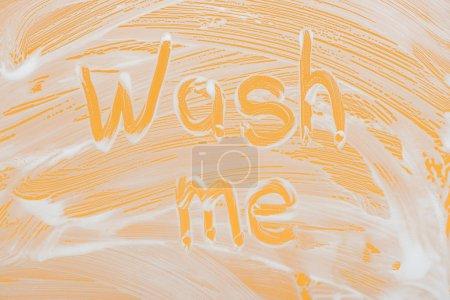 Photo pour Laver moi lettrage manuscrit écrit sur verre avec mousse blanche sur fond orange - image libre de droit
