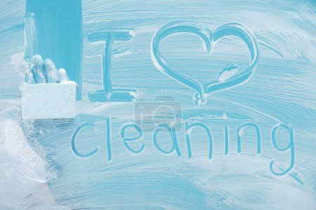 Photo for Partial view of cleaner with sponge near i love cleaning handwritten lettering on glass with white foam on blue background - Royalty Free Image