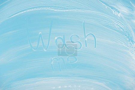 Photo pour Laver moi lettrage manuscrit écrit sur verre avec mousse blanche sur fond bleu - image libre de droit
