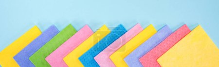 Photo for Panoramic shot of bright multicolored rags on blue background - Royalty Free Image
