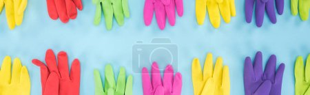 Photo for Panoramic shot of multicolored rubber gloves on blue background - Royalty Free Image