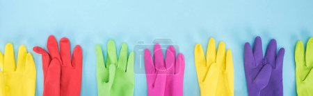 Photo for Panoramic shot of multicolored rubber gloves in row on blue background - Royalty Free Image