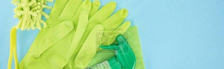 Photo pour Tir panoramique de gants en caoutchouc vert, éponge, chiffon et bouteille de pulvérisation avec détergent sur fond bleu avec espace de copie - image libre de droit