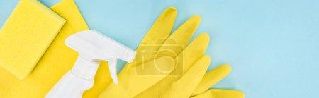 Photo pour Tir panoramique de gants en caoutchouc jaunes, éponge, chiffon et spray sur fond bleu avec espace de copie - image libre de droit