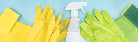 Photo pour Coup panoramique de gants en caoutchouc jaunes et verts, éponges, chiffons et bouteille de pulvérisation avec détergent sur fond bleu - image libre de droit