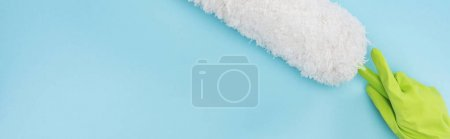 panoramic shot of cleaner in green rubber glove holding duster on blue background
