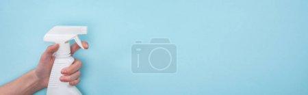 Photo pour Tir panoramique de femme retenant la bouteille blanche de jet avec le détergent sur le fond bleu - image libre de droit