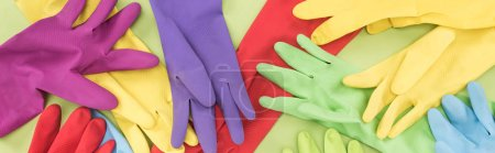 Photo for Panoramic shot of messy scattered multicolored rubber gloves on green background - Royalty Free Image