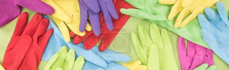 Photo for Panoramic shot of scattered multicolored rubber gloves on green background - Royalty Free Image