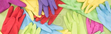 Photo pour Prise de vue panoramique de gants en caoutchouc multicolores éparpillés sur fond vert - image libre de droit