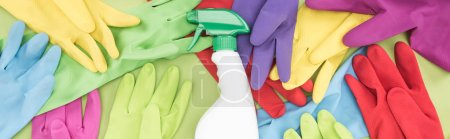 Photo for Panoramic shot of messy scattered multicolored rubber gloves and white spray bottle with cleanser on green background - Royalty Free Image