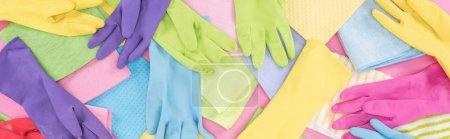 Foto de Foto panorámica de trapos multicolores dispersos desordenados y guantes de goma en el fondo rosa - Imagen libre de derechos
