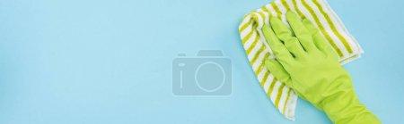 Foto de Panoramic shot of cleaner in green rubber glove holding striped rag on blue background - Imagen libre de derechos