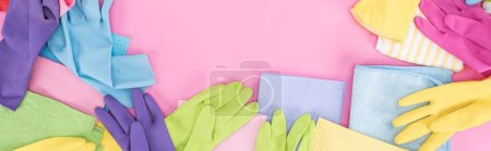 Photo for Panoramic shot of scattered multicolored rags and rubber gloves on pink background with copy space - Royalty Free Image