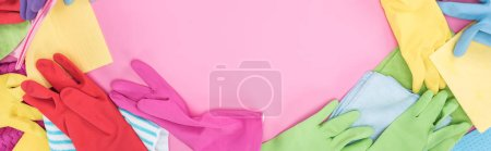Photo for Panoramic shot of multicolored rags and rubber gloves on pink background with copy space - Royalty Free Image