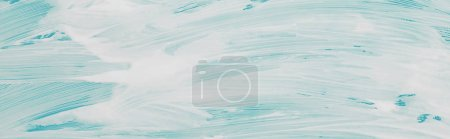 Photo for Panoramic shot of glass covered with white foam on blue background - Royalty Free Image