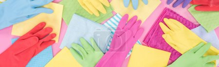 Photo for Panoramic shot of scattered colorful rags and rubber gloves on pink background - Royalty Free Image