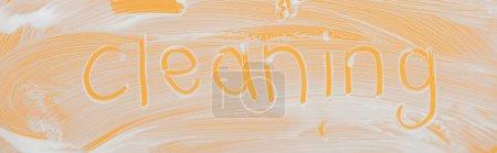 Photo pour Plan panoramique de verre recouvert de mousse blanche sur fond orange avec lettrage de nettoyage - image libre de droit