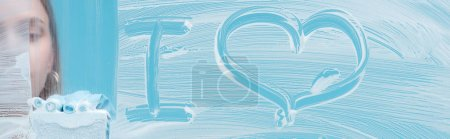 Photo for Panoramic shot of woman with sponge near i love lettering on glass with white foam on blue background - Royalty Free Image