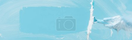 Photo for Panoramic shot of woman in rubber glove cleaning glass with squeegee on blue background - Royalty Free Image
