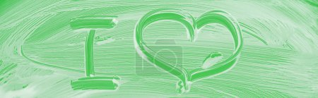 Photo pour Panoramic shot of glass covered with white foam on green background with I letter and heart sign - image libre de droit
