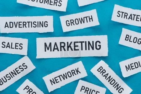 Photo pour Vue du haut des composants du marketing sur des morceaux de papier sur le bleu - image libre de droit
