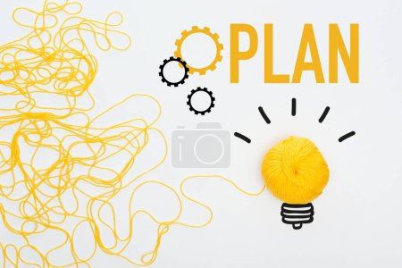 Photo pour Vue du dessus de boule de tricot jaune et fil près du plan de mot sur fond blanc, concept d'entreprise - image libre de droit