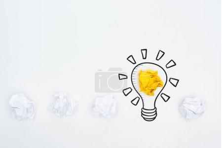 Photo pour Vue de dessus de balles de papier effilochées blanches et jaunes et illustration de l'ampoule sur fond blanc, concept commercial - image libre de droit