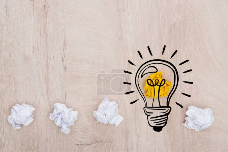 Foto de Top view of crumpled paper balls and illustration of light bulb on wooden table, business concept - Imagen libre de derechos