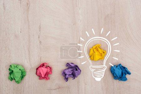 Photo pour Vue de dessus des boules de papier froissées multicolores et illustration d'ampoule sur la surface en bois, concept d'entreprise - image libre de droit