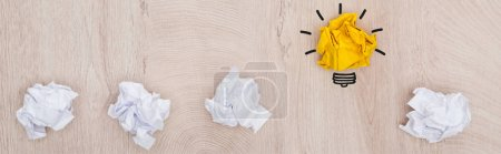 panoramic shot of crumpled paper balls and light bulb illustration on wooden surface, business concept